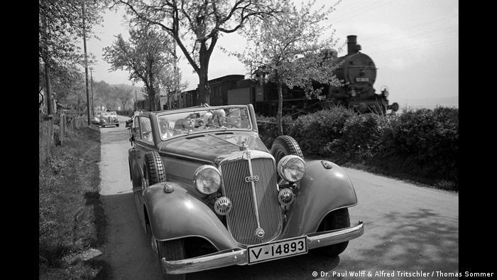 Auto steht auf einer Straße während im Hintergrund ein Zug anrauscht (Dr. Paul Wolff & Alfred Tritschler / Thomas Sommer)