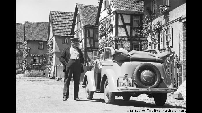 Ein Mann steht bewundernd neben einem Auto, das in einer Straße mit pflanzenumrankten Fachwerkhäusern parkt (Dr. Paul Wolff & Alfred Tritschler / Thomas Sommer)