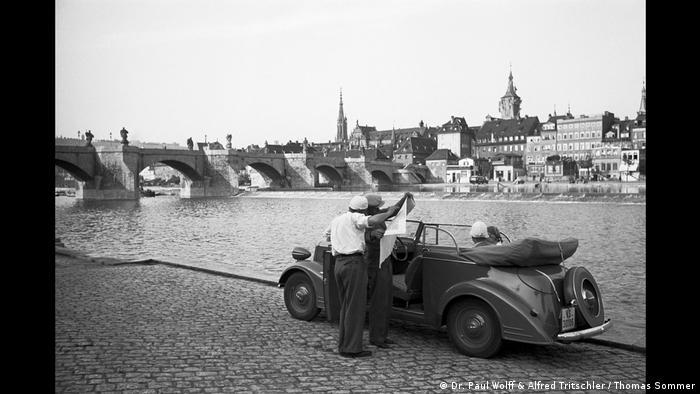 Zwei Männer vor einem parkenden Auto, das nahe der Alten Mainbrücke am Mainufer in Würzburg steht (Dr. Paul Wolff & Alfred Tritschler / Thomas Sommer)