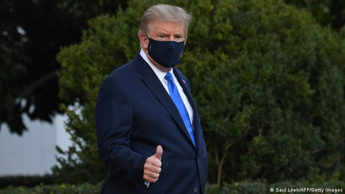 Trump wears a black face mask and a dark blue suit as he walks to a helicopter. He is profile in the picture. He is giving a thumbs up to the camera with his right hand.