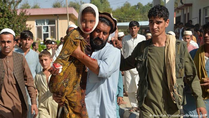 An injured youth (C-L) is carried to a hospital following a car bomb attack that targeted a government building, in the Ghani Khel district of Nangarhar province, about 35 km from Jalalabad on October 3, 2020