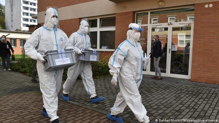 Члены избиркома на региональных выборах в Чехии в костюмах, призванных защитить их от заражения коронавирусом, 2 октября 2020 года