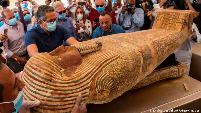 An expert examines a wooden sarcophagus