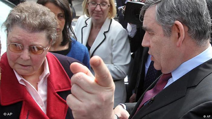 Gordon Brown points his finger at the camera while speaking to a woman who looks away (AP)