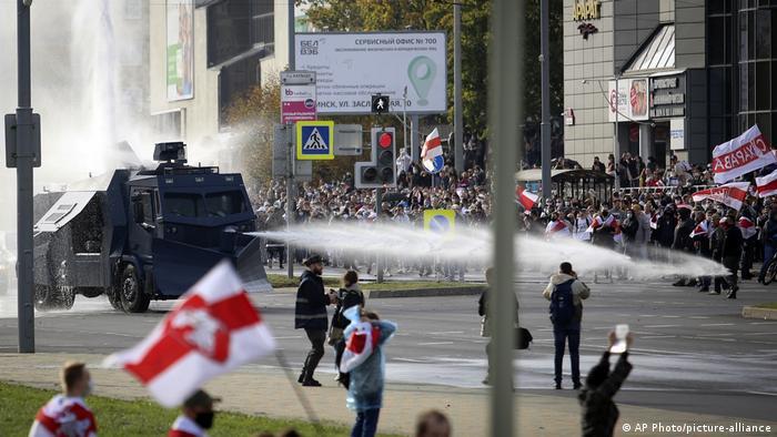Veículo lança jato de água contra manifestantes em rua