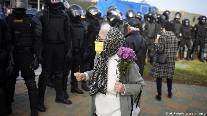 Пожилая женщина в защитной маске и с букетом в руках перед цепью омоновцев на акции протеста в Минске