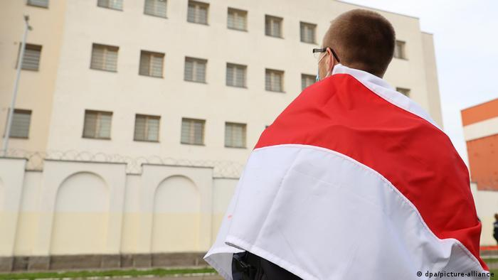 A protester stands outside a detention center in Minsk on Sunday