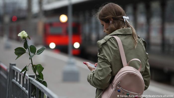 Девушка держит в руке смартфон, рядом белая роза