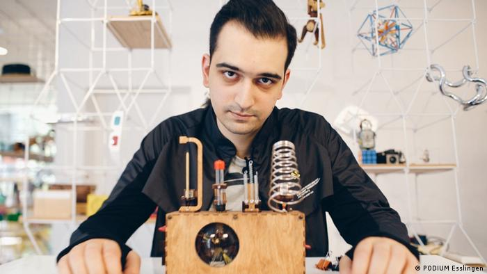 The artist in a room that looks like a laboratory with a wooden box with wires and coils sticking out of it in front of him (PODIUM Esslingen)