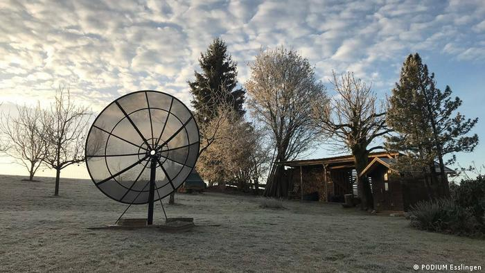 A radio telescope in front of a small wooden structure outdoors (PODIUM Esslingen)