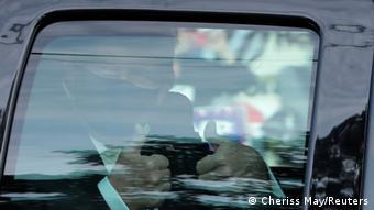 Дональд Трамп в маске показывает большие пальцы из машины