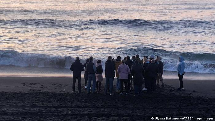 Group of people huddle at the shoreline of Khalaktyrsky beach in Russia's Far East