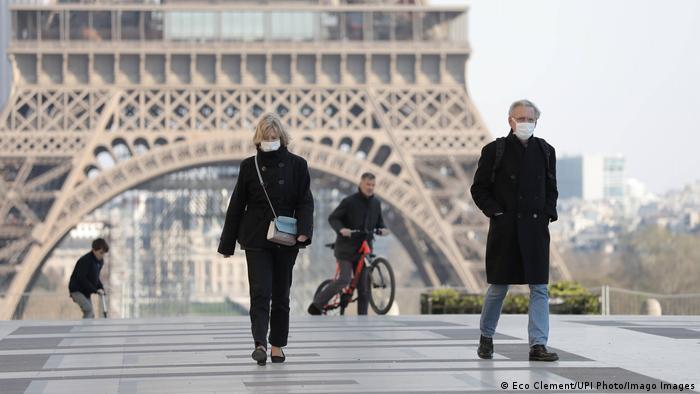 Pessoas de máscara diante da Torre Eiffel