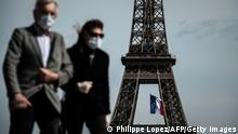People wearing face masks in front of the Eiffel Tower (Philippe Lopez/AFP/Getty Images)