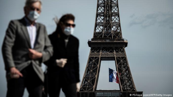 Casal de máscara passa em frente à Torre Eiffel, em Paris.
