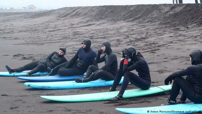Surfers from the Snowave surf school in Russia's Far East sit on their boards on the shore