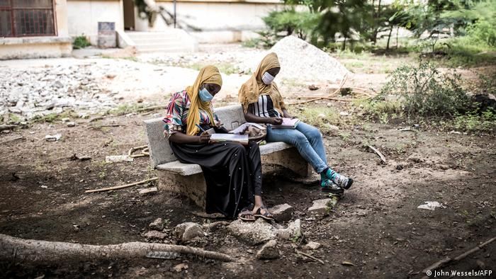 Two university students in Dakar sit on a bench with books on their laps