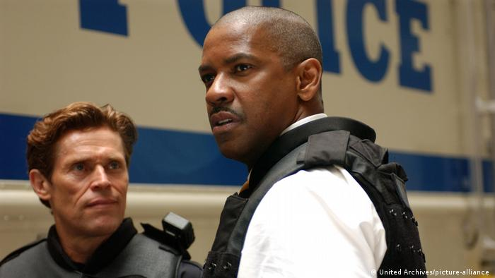 Willem Dafoe blickt Filmpartner Dezel Washington in Inside Man an.