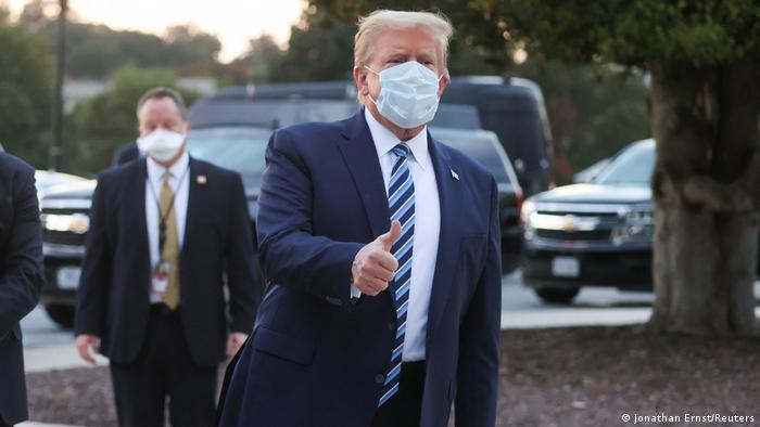 Donald Turmp mit Gesichtsmaske zeigt den Daumen hoch