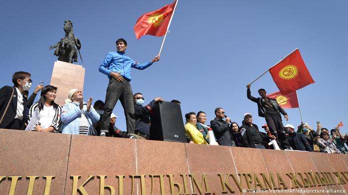 Люди с флагами в Бишкеке во время протестов в Киргизии 5 октября