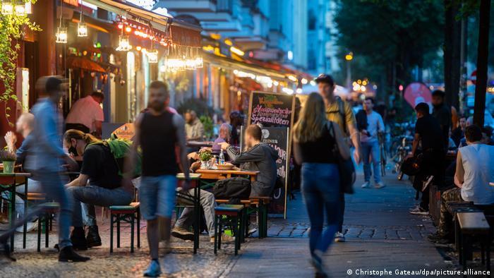 Menschen in Bars und auf dem Gehweg in der Abenddämmerung