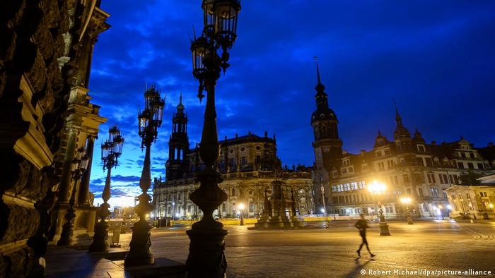 Jogger running across square in Dresden in early morning hours, with dark blue sky and city lights