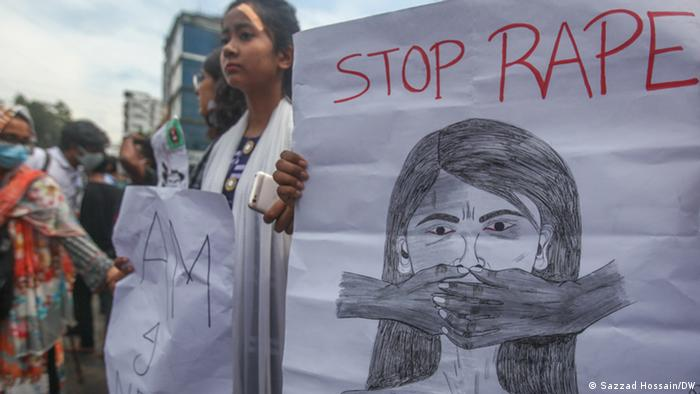 An unseen person holds a sign which reads 'stop rape'