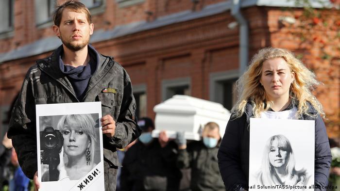 Der Sohn und die Tochter von Irina Slawina halten während des Begräbnisses von Irina Slawina Bilder von ihrer Mutter in der Hand