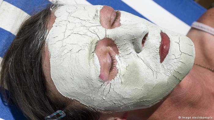 Eine Frau mit einer kosmetischen Gesichtsmaske aus Creme.