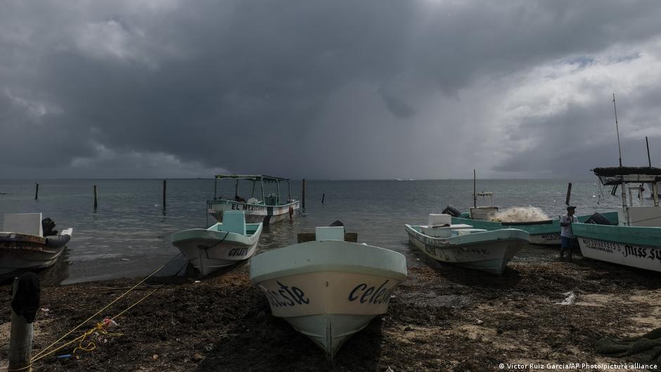 En el horizonte, el huracán Delta se acerca desde detrás de los barcos pesqueros en tierra.