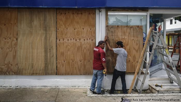 Men board up a Telcel phone store as Hurricane Delta approaches Puerto Juarez, Mexico