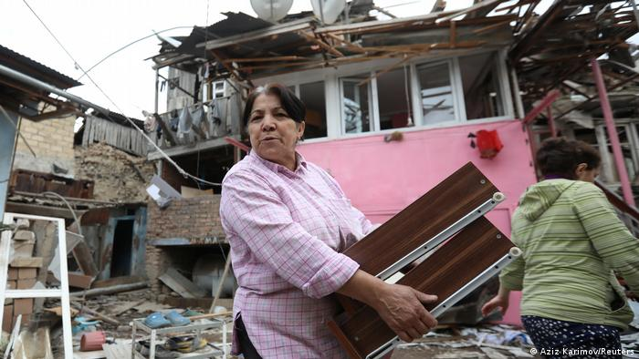 A woman carries belongings as she walks past a house damaged by recent shelling
