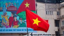 Vietnam l Fahne weht vor Propagandaplakat in Ho Chi Minh City