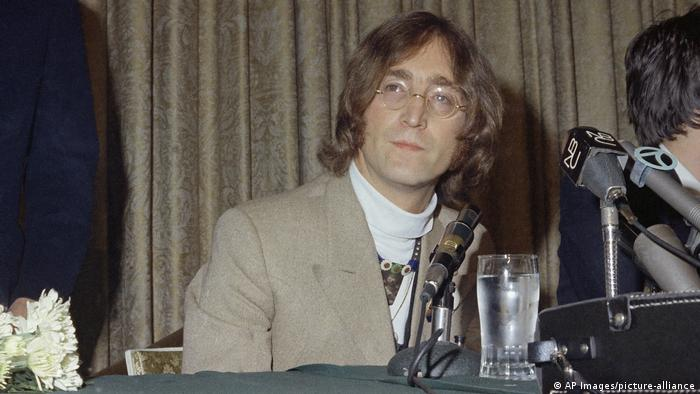 John Lennon in 1971 at a table with a microphone and a glass of water (AP Images/picture-alliance)