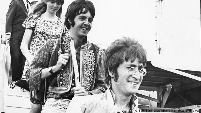 Paul McCartney and John Lennon smiling as they walk out of an airplane (Solo Syndication/Daily Mail/picture-alliance)