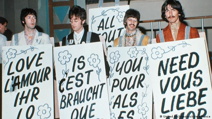 The Beatles with signs with words in different languages making up All you need is love (United Archives/picture-alliance)