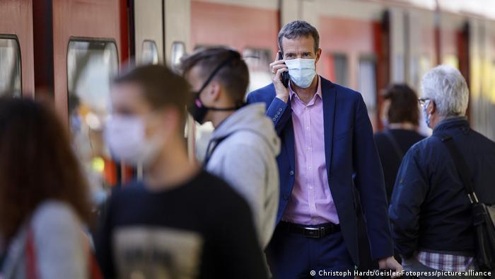 Pessoas de máscara em estação de trem em Colônia