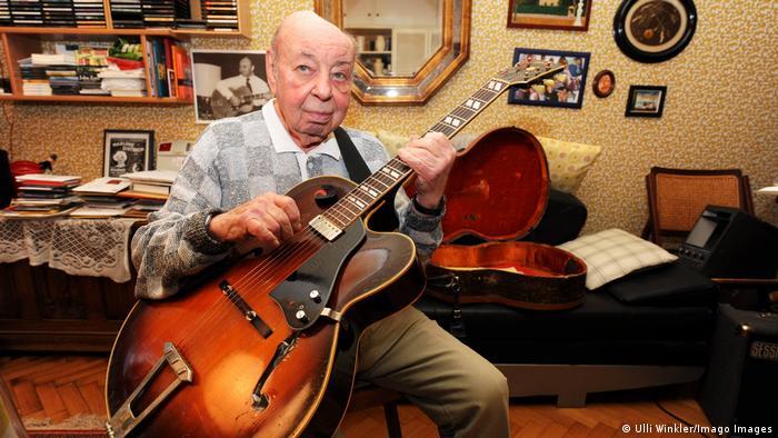 Coco Schumann sitzt mit Gitarre auf dem Schoß im Wohnzimmer und blickt in die Kamera. (Ulli Winkler/Imago Images)