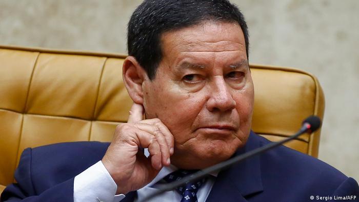 Mourão, de terno, sentado em uma cadeira, com o dedo indicador da mão direita atrás da orelha. À sua frente está um microfone.