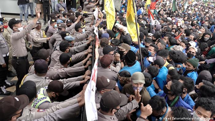 Demonstrators clash with police during a protest against the government's labor reforms in Indonesia