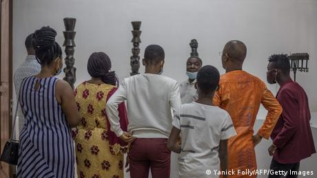 Visitors listen to a museum guide in Ouidah