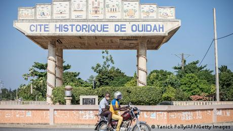Two men ride past the entrance gate to the city of Ouidah on a motorbike