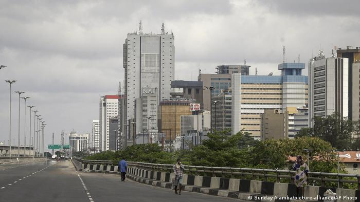 A handful of pedestrians walk along a deserted highway in Lagos
