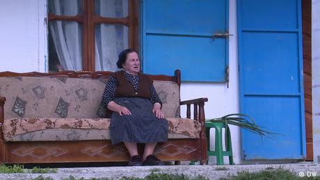 An older woman sits on her porch