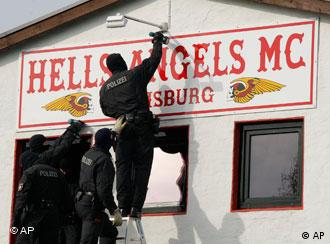 Police remove a 'Hell's Angels' sign from a building