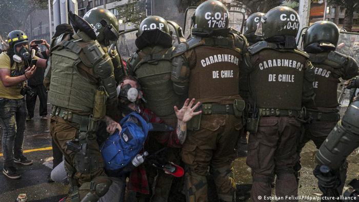 Foto de agentes de Carabineros mientras detienen a una persona durante las protestas