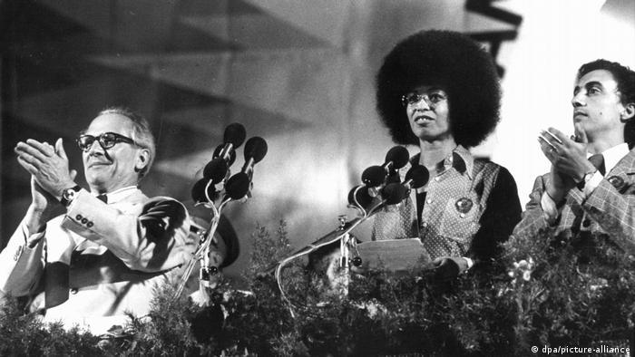 Angela Davis mit Afro-Frisur lächelt auf einer Bühne, hinter Mikrofonen stehend, links neben ihr klatscht SED-Chef Erich Honecker, 1973 in Ost-Berlin (Foto: dpa/picture-alliance).
