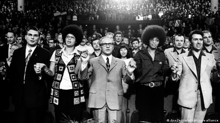 Großer Zuschauersaal mit stehenden Menschen, in der ersten Reihe ist unter anderem die junge Angela Davis in Afro-Frisur zu sehen, die die Hand von Erich Honecker hält (Foto: dpa-Zentralbild/picture-alliance).
