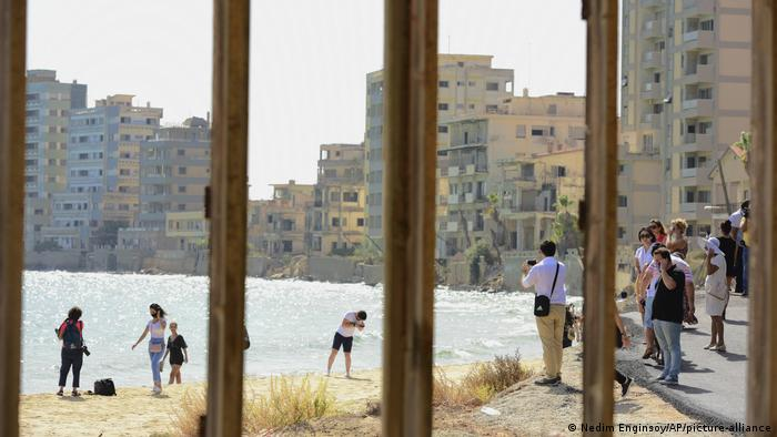 People stand at the beachside dwarfed by the abandoned hotels of Varosha