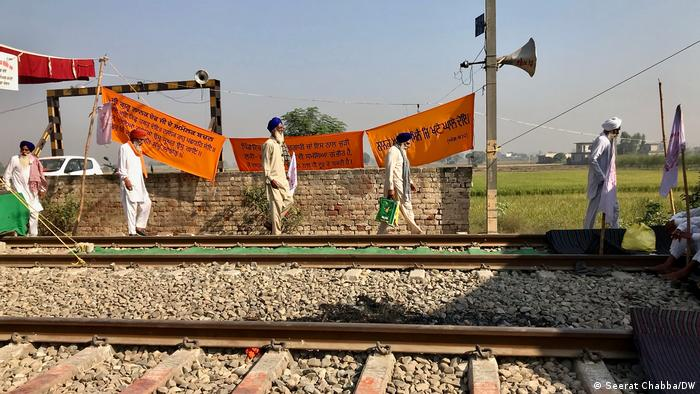 Farmers in Punjab walk next to train tracks